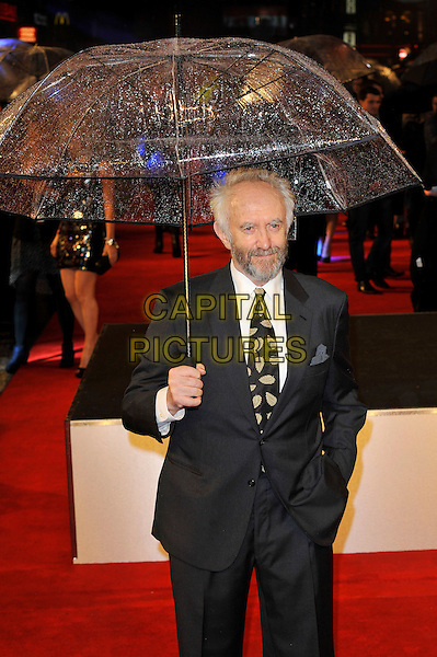 "Jonathan Pryce.The ""G.I. Joe 2: Retaliation"" UK film premiere, Empire cinema, Leicester Square, London, England..March 18th, 2013.suit jacket white shirt yellow print tie beard facial hair leaf leaves black half length hand in pocket umbrella .CAP/MAR.© Martin Harris/Capital Pictures."