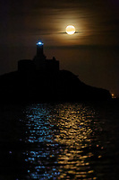 A full moon, known as Harvest Moon is seen rising over Mumbles Lighthouse, near Swansea, Wales, UK. Tuesday 25 September 2018