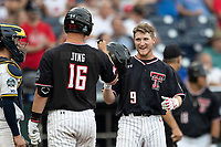 Texas Tech Red Raiders outfielder Dylan Neuse (9) is greeted by teammate Josh Jung (16) after scoring during Game 1 of the NCAA College World Series against the Michigan Wolverines on June 15, 2019 at TD Ameritrade Park in Omaha, Nebraska. Michigan defeated Texas Tech 5-3. (Andrew Woolley/Four Seam Images)