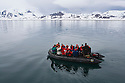 Tourists in zodiac cruising on ocean near frozen shore line; Svalbard, Norway