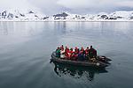 Tourists in zodiac cruising on ocean near frozen shore line; Svalbard, Norway