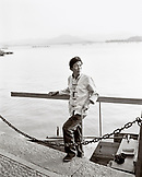 CHINA, Hangzhou, boat owner takes a break betwen lake tours at West Lake (B&W)