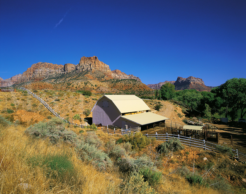Ranch buildings and distant rock peaks at Springdale at the entrance to Zion Canyon, Utah, US