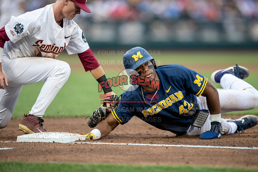 Michigan Wolverines designated hitter Jordan Nwogu (42) dives back before Florida State Seminoles first baseman Carter Smith (35) tags him during the NCAA College World Series on June 17, 2019 at TD Ameritrade Park in Omaha, Nebraska. Michigan defeated Florida State 2-0. (Andrew Woolley/Four Seam Images)