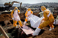 A burial team, dressed in PPE (personal protection equipment) at the King Tom cemetery, lower the body of a person who is suspected to have died from ebola into one of a group of pre-dug graves. Due to the rapid increase in burials, caused by the ebola crisis, the cemetery is being enlarged and parts of a nearby rubbish dump is also being used to bury the dead.