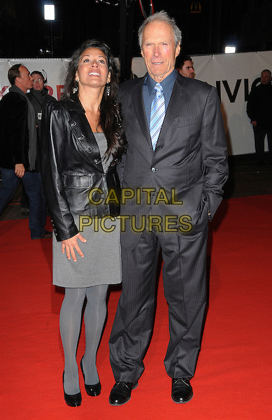 "DINA RUIZ & CLINT EASTWOOD.Attending the ""Invictus'"" UK Film Premiere at the Odeon West End cinema, Leicester Square, London, England, January 31st, 2010. .arrivals full length married husband wife couple grey gray dress tights black shoes leather jacket blue tie shirt pinstripe hand in pocket .CAP/CAS.©Bob Cass/Capital Pictures"