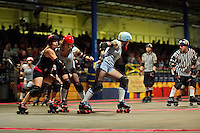 Etta Maims (red hat) blocks an opponent for Shellby Shattered during a roller derby bout in Wilmington, Massachusetts. Roller derby is an American contact sport, popular with young women, which combines both athleticism and a satirical punk third-wave feminism aesthetic.