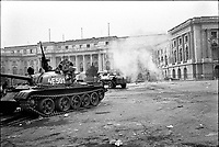 """ROMANIA, Pta. Palatului, today Pta. Revolutiei, Bucharest, 24.12.1989<br /> People rise against Ceausescu. The dictator has fled the city on dec. 22. At the central square intense figting with unidentifiable """"terrorists"""" has been going on. Almost all buildings are damaged or partly destroyed. Army T-55 tanks.<br /> © Andrei Pandele / EST&OST"""