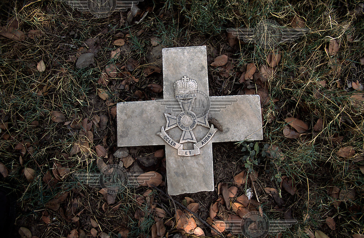Colonial remnant - The crest of a British regiment (King's Royal Rifle Brigade) is carved into the broken cross headstone on a grave in the decaying christian Nicholson Cemetery.