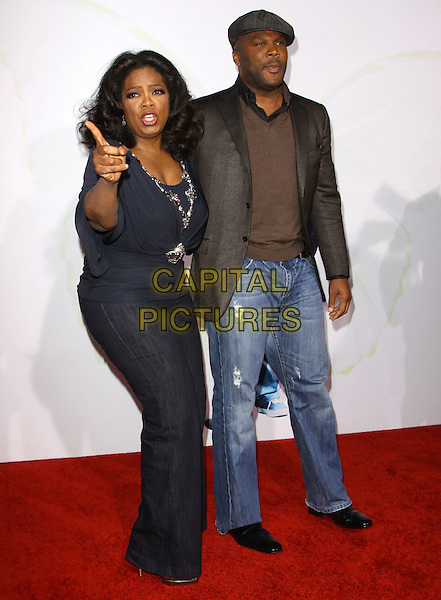 """OPRAH WINFREY & TYLER PERRY .at the 2009 AFI Film Festival Premiere of """"Precious"""" held at Grauman's Chinese Theatre, Hollywood, California, USA, .1st November 2009. .full length cap hat brown jacket sweater jumper jeans denim navy blue beaded trim silver embellished jewel encrusted top hand finger gesture side.CAP/ADM/KB.©Kevan Brooks/AdMedia/Capital Pictures."""