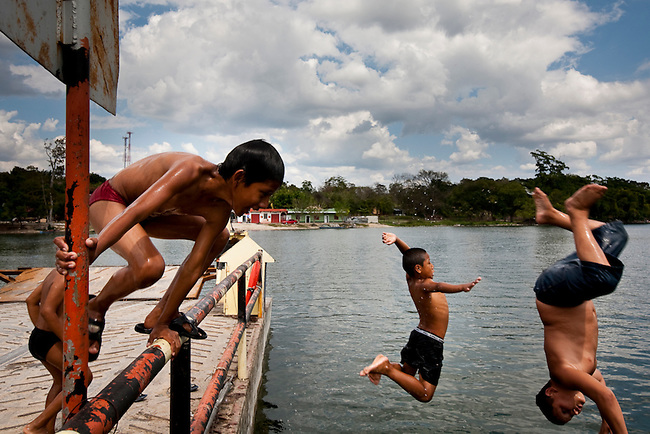 Boys play on the barge that supplies access to an oil well inside the Mayan Biosphere, the barge also supplies hundreds of ranching families living illegally inside the Mayan Biosphere.