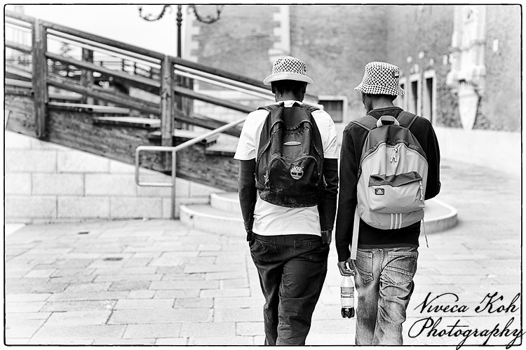 Two men walking towards bridge, Venice, Italy.