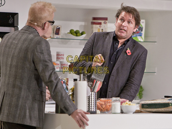 Chris Evans and James Martin.BBC Good Food Show London 2012, Olympia, Kensington, London, England..November 10th 2012.half length grey gray suit jacket glasses hand arm side profile funny mouth open.CAP/MM/PP.©Mike Mustard/PP/Capital Pictures