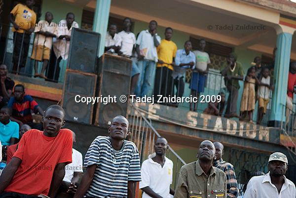 Spectators watch a soccer game during a tournament at Pece Stadium, Gulu District.