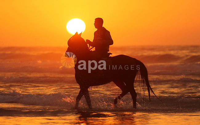 A Palestinian man rides a horse at the beach during sunset in Gaza City on January 3, 2018. Photo by Ashraf Amra