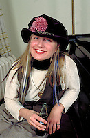 Woman age 23 smiling and wearing black hat with purple flower.  Minneapolis  Minnesota USA