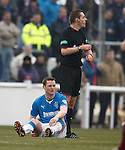 Jon Daly sitting injured on the grass holding his hamstring