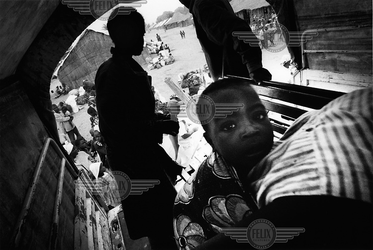 A child sits in the back of a truck onto which refugees are being helped into before they are taken on the last stage of their journey home. .The immediate post-conflict period in Angola from April 2002 has seen hundreds of thousands of refugees return to the country after more than 30 years of civil unrest.