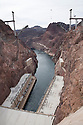 Below lies the hydroelectric power station at Hoover Dam while the Colorado River Bridge is under construction in the background. Hoover Dam spans the Colorado River at the border between Nevada and Arizona. Lake Mead is the reservoir behind the dam. The dam's hydroelectric power station generates, on average, about 4 billion kilowatt-hours of power a year and is distributed to Nevada, Arizona, and California. It meets the energy needs of approximately 1.3 million people. Lake Mead is also a significant source of municipal drinking water and agricultural water for the region. Almost a decade of drought and increased water demand have brought Lake Mead near its lowest level in over 40 years. Photo taken February 2009.
