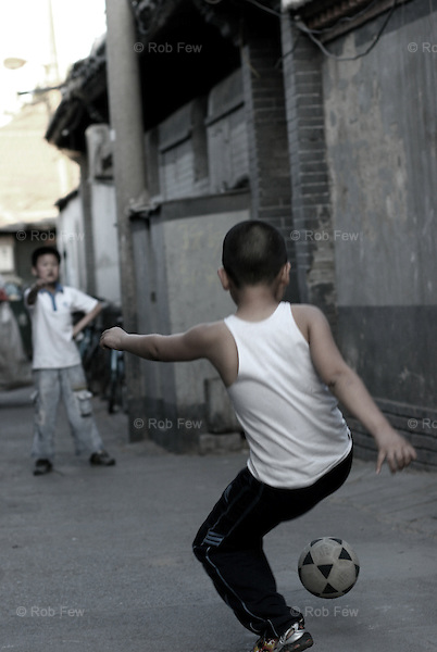The last two kids in the world without a Playstation play football in a Beijing hutong.