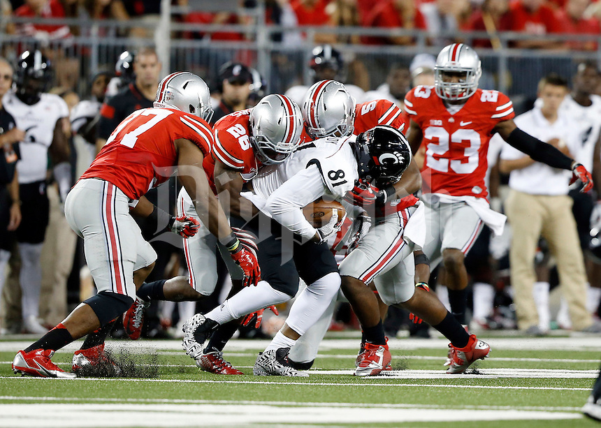 Ohio State defenders, from left, linebacker Joshua Perry (37), cornerback Armani Reeves (26), linebacker Raekwon McMillan (5) and safety Tyvis Powell (23) team up to stop Cincinnati Bearcats tight end DJ Dowdy (81) during the fourth quarter of the NCAA football game at Ohio Stadium in Columbus on Sept. 27, 2014. (Adam Cairns / The Columbus Dispatch)