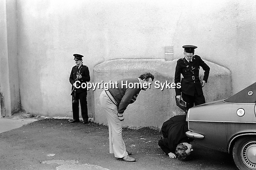 Derry, Northern Ireland. 1979<br /> An armed Royal Ulster Constabulary officer stands guard, while colleagues check for a car bomb, as the owner looks on.