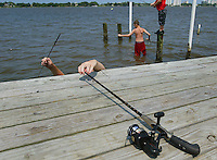 "Hands appear eerily over the edge of a dock along Riverside Drive in Holly Hill, foreground, as Chris Powers, 14, [cq] reaches over to grab his pole so he can head out to a group of pilings to fish with his brother Jonathan Powers, 11, [cq] right, and his friend John Valderrama, 14, [cq] middle as the group spends their afternoon fishing Monday July 12, 2004. The trio enjoys fishing and do it as oftern as they can. Monday there was a catch, so to speak. Chris and his brother Jonathan had to clean their room in order to gain the privaledge of the outing. ""This morning we had to clean our room, it was horrible, but we got to come fishing this afternoon"", said Chris as he explained how usually they can fish if their chores are done for the day.(Kelly Jordan)..**FOR STAND ALONE FEECH**"