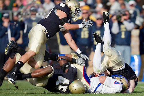 Tulsa quarterback G.J. Kinne (#4) is sacked by Notre Dame defenders led by outside linebacker Darius Fleming (#45) during NCAA football game between Tulsa and Notre Dame.  The Tulsa Golden Hurricane defeated the Notre Dame Fighting Irish 28-27 in game at Notre Dame Stadium in South Bend, Indiana.