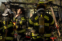 Santa Rosa firefighter Zane Brown, center, opens his collar to cool down after extinguishing a structure fire on Bellevue Avenue in Santa Rosa, Calif., on February 27, 2013.  (Alvin Jornada / The Press Democrat)