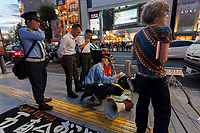 Police officers check details with the organisers of  a small protest against the staging of the Olympic Games in Shinjuku, Tokyo, Japan Friday June 30th 2017. Though mostly popular with the Japanese population he staging of the 2020 Olympic Games in Tokyo is felt by some to be a waste of money when the economy is bad, causing increasing poverty rates and with problems in the Tsunami damaged North East coast still not fully resolved.