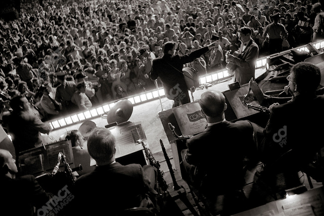 At Russwood stadium mid performance. Scotty Moore to Elvis's right, Bill Black to his left on bass and DJ Fontana on drums between 2 foreground musicians.The stand Elvis band trio. Musicians uppermost in the frame are house musicians there for other performances, Memphis, Tennessee, July 4, 1956