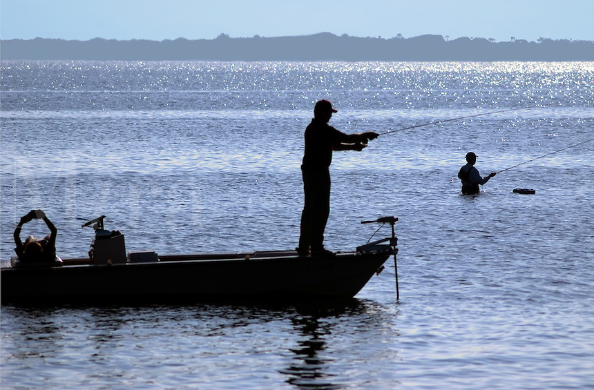A man stands fishing from a boat in the Indian River near Grant, Florida, while his wife reads a book in the strern of the boat and another man with waders stands in the same area, fishin