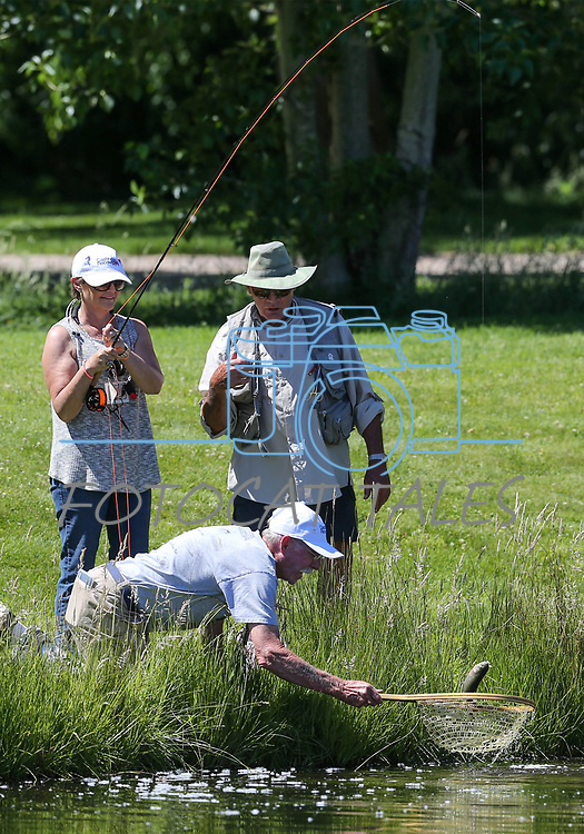 Dave Sorokwasz, right, and Marty Wright, with net, help as breast cancer survivor Michele Kimzey, of Placerville, reels in a fish during a Casting for Recovery retreat in Gardnerville, Nev., on Friday, June 30, 2017. The nationwide program, hosted locally with Carson Tahoe Cancer Center, pairs cancer survivors with fly-fishing guides.  <br />