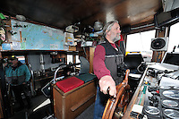 Captain David Janka steers the M/V Auklet as it departs from the town of Cordova, Prince William Sound, Southcentral Alaska on a spring day in early May. Crewman Dan Logan is at left, and John DeLapp (obscured) is a center. MR/PR