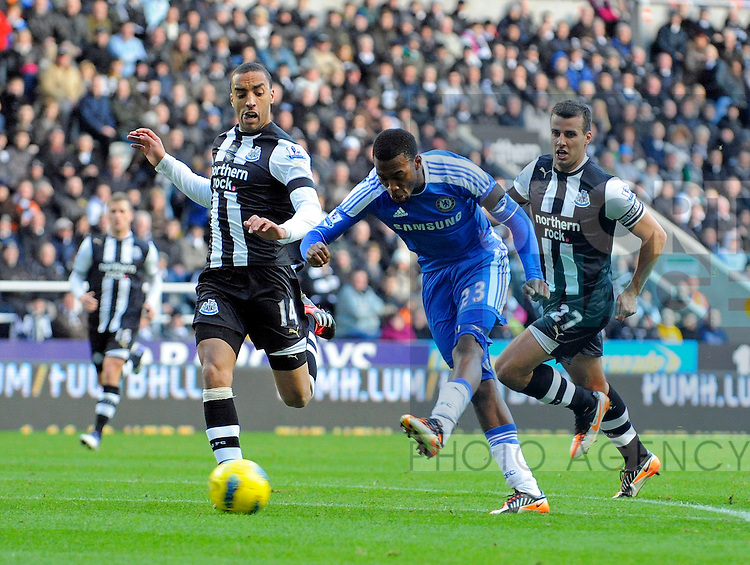 Daniel Sturridge of Chelsea FC (C) gets a shot at goal past James Perch of Newcastle United (L) during the Premier League football match between Newcastle United and Chelsea FC on 3 December 2011, at St. James' Park, Newcastle upon Tyne, England.