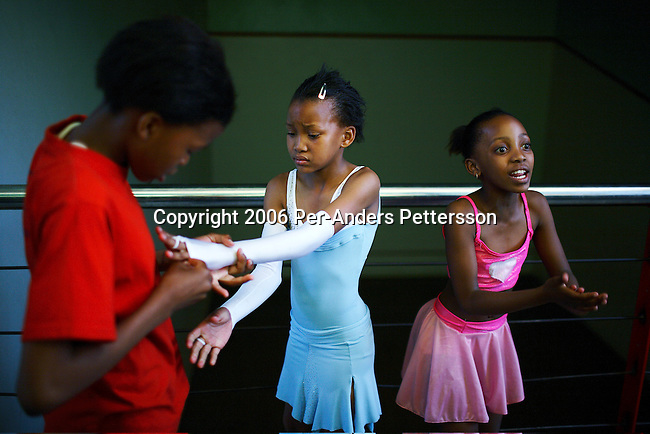 SOWETO, SOUTH AFRICA OCTOBER 25: Young ballroom dancers dress before a dress rehearsal in a community hall in Pimville Community center on October 25, 2006 in Soweto, Johannesburg, South Africa. Ballroom dancing is very popular sport in the township and all over the country. Soweto is South Africa?s largest township and it was founded about one hundred years to make housing available for black people south west of downtown Johannesburg. The estimated population is between 2-3 million. Many key events during the Apartheid struggle unfolded here, and the most known is the student uprisings in June 1976, where thousands of students took to the streets to protest after being forced to study the Afrikaans language at school. Soweto today is a mix of old housing and newly constructed townhouses. A new hungry black middle-class is growing steadily. Many residents work in Johannesburg, but the last years many shopping malls have been built, and people are starting to spend their money in Soweto.  .(Photo by Per-Anders Pettersson/Getty Images).