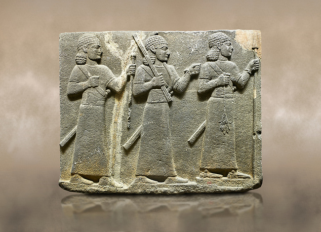 Photo of Hittite relief sculpted orthostat stone panel of Royal Buttress Basalt, Karkamıs, (Kargamıs), Carchemish (Karkemish), 900-700 B.C. Warriors. Anatolian Civilisations Museum, Ankara, Turkey.<br /> <br /> Three figures each with a long dress, a thick belt and curly hair. The figure in front holds a spear with a broken tip in his left hand and a leafy branch in his right hand. The figure in the middle made his left hand a fist, and he carries a tool with his right hand at the level of his head. They are followed with a figure holding a sceptre in his left hand. All three have each a long sword at their waist. <br /> <br /> Against a brown art background.