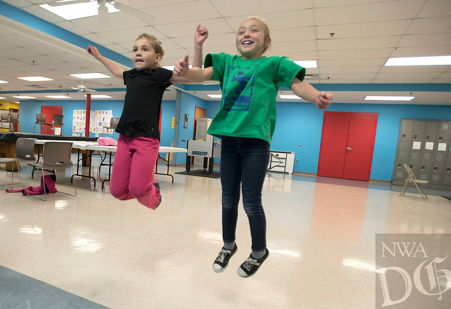 NWA Democrat-Gazette/J.T. WAMPLER Sisters Zypporah Wyles, 8, left, and Zoey Wyles, 7, play an interactive video game Monday Jan. 18, 2016 at the Rogers Activity Center. The girls were spending some time at the center because Rogers schools were closed due to winter weather. The game, River Rush, is controlled by body motion and hand gestures.