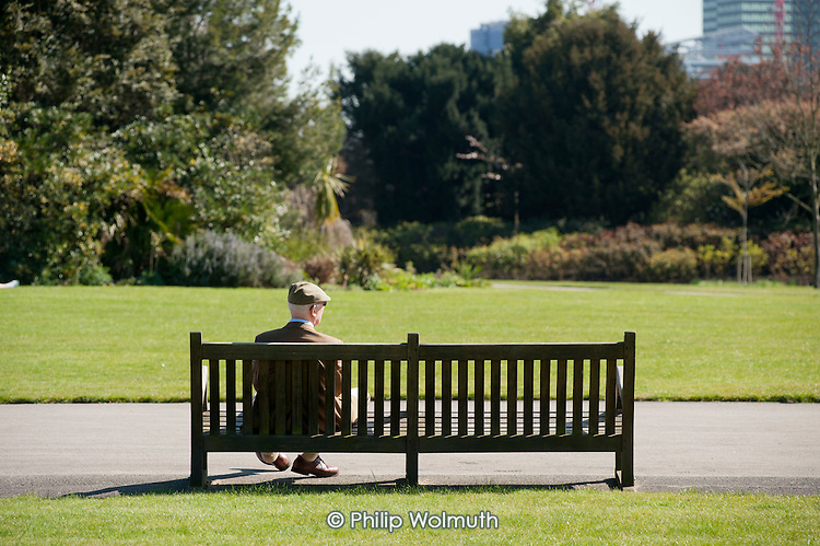 Elderly man sitting on a bench, Regent's Park, London.