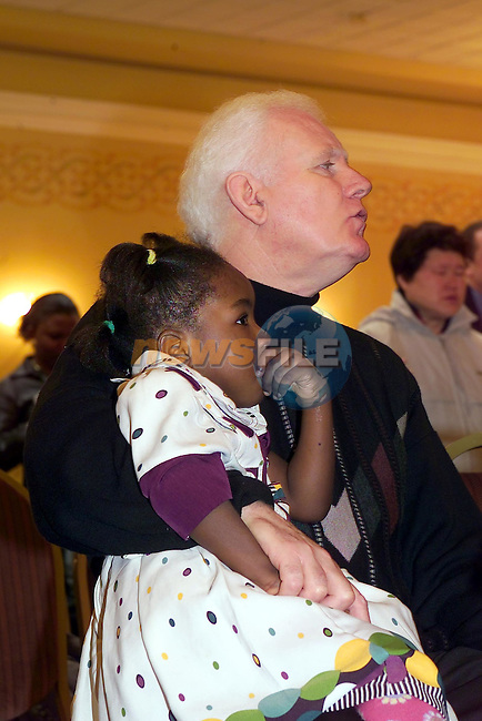 Retired Superentendent Pat O'Boyle holding one of the refugee children that attend the Solid Rock church in Drogheda, as his wife marcella preaches to the congeration..Picture Fran Caffrey Newsfile.