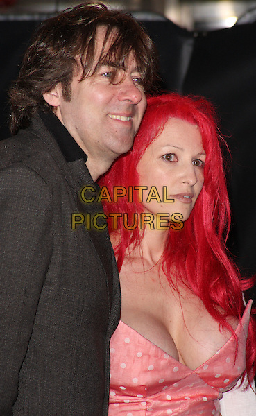 JONATHAN ROSS & JANE GOLDMAN .UK Premiere of 'Kick-Ass' at the Empire cinema, Leicester Square, London, England, UK, March 22nd 2010.arrivals half length married couple husband wife jacket grey gray  brown blazer cleavage pink peach polka dot strapless Vivienne Westwood white low cut coral profile smiling side .CAP/ROS.©Steve Ross/Capital Pictures.