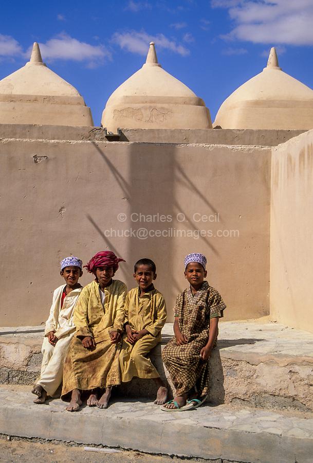 Jalan Bani Bu Ali, Oman.  Pre-teen Omani Boys Sitting outside the Mosque of Rashid bin Hamouda, Jalan Bani Bu Ali.