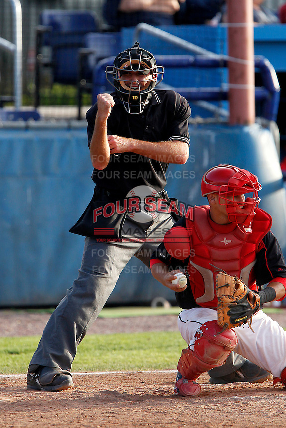 Home plate umpire Brian Miller makes a call behind catcher Juan Castillo #35 during the first game of a doubleheader between the Batavia Muckdogs and Williamsport Crosscutters at Dwyer Stadium on August 23, 2011 in Batavia, New York.  Batavia defeated Williamsport 2-1.  (Mike Janes/Four Seam Images)