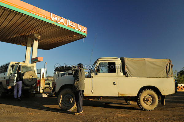Africa, Morocco, Western Sahara, nr. Laayoune. Land Rover Santana Pick-Up at a petrol station. --- No releases available. Automotive trademarks are the property of the trademark holder, authorization may be needed for some uses. --- Info: From the mid 1950's untill the early 1990's the english Land Rover was also built under license in Spain. The spanish company Metalurgica de Santa Ana (later to become Santana Motor SA), was producing Land Rovers in the beginning from CKD kits, but local content was gradually increased until the Santanas (this is how they were called) were 100 per cent locally manufactured.