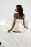 African American woman wearing negligee sitting in bed
