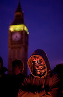 A protestor stands by a fire to keep warm on Parliament Square outside the Houses of Parliament during a student demonstration in Westminster, central London on the day the government passed a bill to increase university tuition fees.