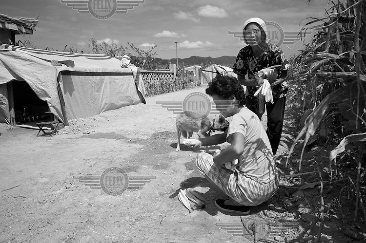 Women prepare a meal near temporary tarpaulin shelters in Pongchon county, DPRK during a field visit by national and international Red Cross officials on Saturday August 27 2011. Consecutive floods caused by heavy rainfall and strong winds, together with the impact of typhoon Muifa which struck in early August, resulted in the destruction or severe damage of over 9,500 houses, rendering more than 25,000 people homeless between June 23 and August 9, according to data provided by the DPRK government. While flood damage was reported throughout the country, south and north Hwanghae provinces have been worst hit by the repeated flooding, leaving an already vulnerable population in a critical condition.  Photo by Morten Hvaal/Felix Features for IFRC.