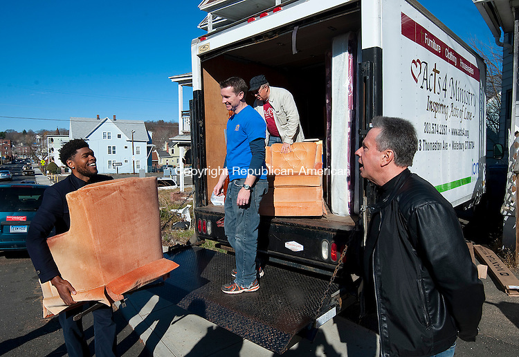 WATERBURY, CT--- -112115JS18--Ryan Gomes, left, with the help of  Acts 4 Ministries board members Tim Blankenshop and David Rogers, center, and Program Coordinator for Hoops For Hearts, Brian McBride, right, unload a truck to one of six families in Waterbury on Saturday. The families received furniture and beds along with complete Thanksgiving dinners from Acts 4 Ministries; Ryan Gomes and his non-profit foundation Hoops for Heart Hearth and the Greater Waterbury Interfaith Ministries, Inc with volunteer efforts from Walnut Hill Church.  Jim Shannon Republican-American