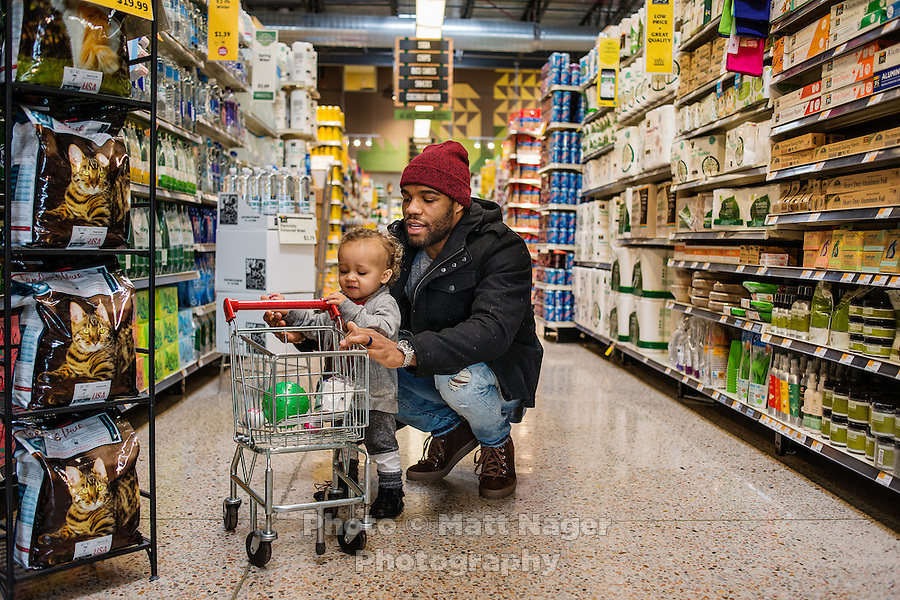 Olympic Gold champion wrestler Jordan Burroughs (cq) and his son Beacon Burroughs (cq, age 19 months) shopping at Whole Foods in Lincoln, Nebraska, Friday, February 12, 2015. Burroughs is training for the upcoming 2016 olympic games in Rio de Janeiro, Brazil where he hopes to win another gold medal. <br /> <br /> Photo by Matt Nager