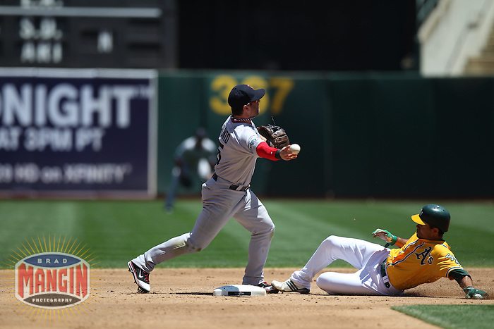 OAKLAND, CA - JULY 4:  Nick Punto #5 of the Boston Red Sox turns a double play at second base against the Oakland Athletics, forcing out A's base runner Coco Crisp #4 during the game at O.co Coliseum on Saturday, July 4, 2012 in Oakland, California. Photo by Brad Mangin